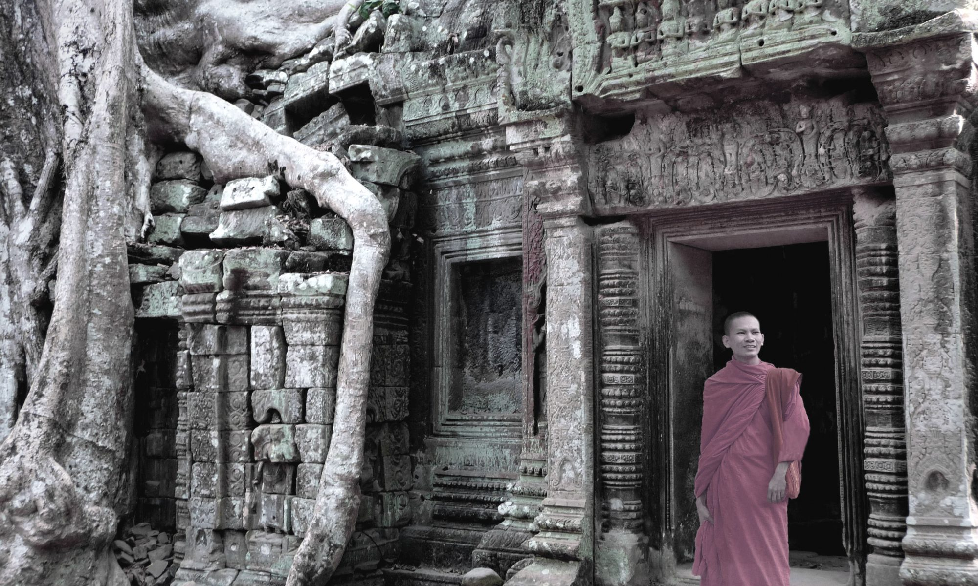 A Buddhist monk standing in the Ta Prohm Temple in Kambodia